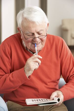 Senior Man Relaxing In Chair At Home Completing Crossword Stock Photo - 9911308