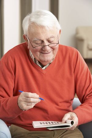 Senior Man Relaxing In Chair At Home Completing Crossword Stock Photo - 9911241