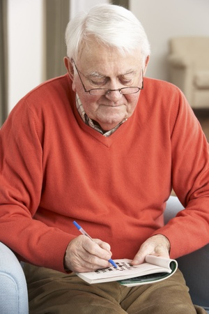 residental care: Senior Man Relaxing In Chair At Home Completing Crossword