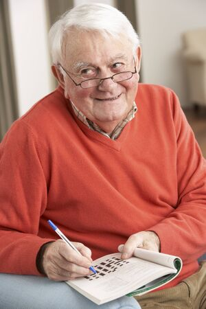 Senior Man Relaxing In Chair At Home Completing Crossword Stock Photo - 9911216