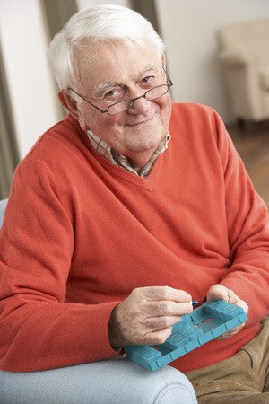 Senior Man Sorting Medication Using Organiser At Home Stock Photo - 9911322