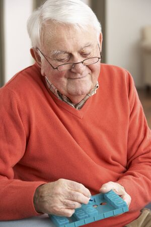 residental care: Senior Man Sorting Medication Using Organiser At Home