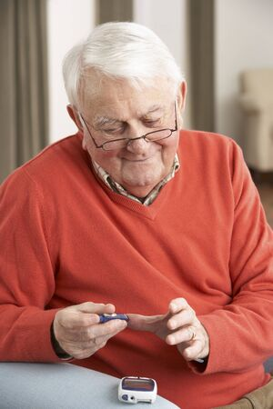 Senior Man Checking Blood Sugar Level At Home Stock Photo