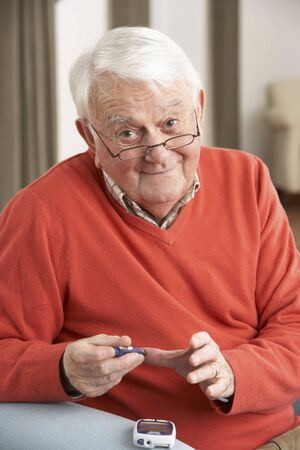 diabetes: Senior Man Checking Blood Sugar Level At Home Stock Photo