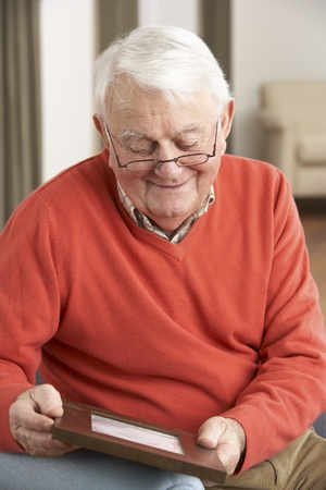 residental care: Senior Man Looking At Photograph In Frame
