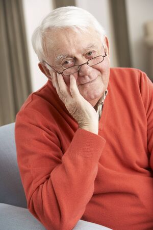 residental care: Senior Man Relaxing In Chair At Home Stock Photo