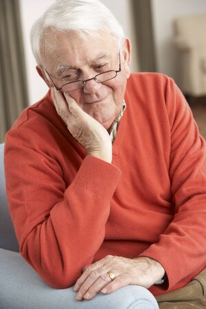 residental care: Senior Man Looking Sad In Chair At Home