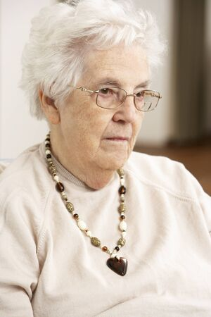 residental care: Senior Woman Looking Sad In Chair At Home
