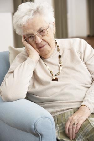 Senior mujer mirando triste en silla en casa