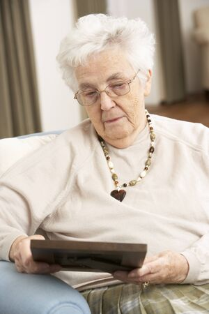residental care: Senior Woman Looking At Photograph In Frame Stock Photo