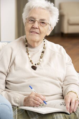 residental care: Senior Woman Relaxing In Chair At Home Completing Crossword