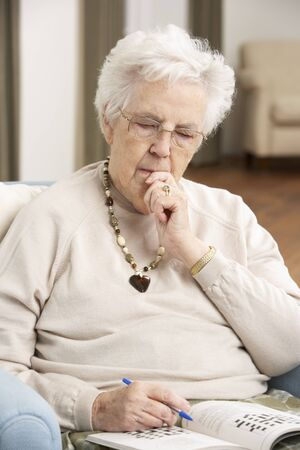 Senior Woman Relaxing In Chair At Home Completing Crossword photo