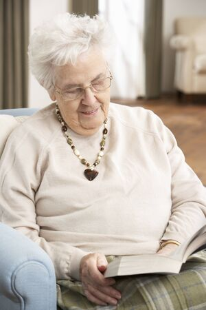 Senior Woman Relaxing In Chair At Home Reading Book Stock Photo - 9911380