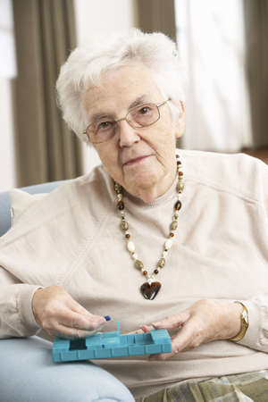 residental care: Senior Woman Sorting Medication Using Organiser At Home