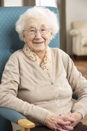 Senior Woman Relaxing In Chair At Home Stock Photo
