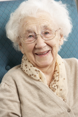 Senior Woman Relaxing In Chair At Home Stock Photo - 9911146