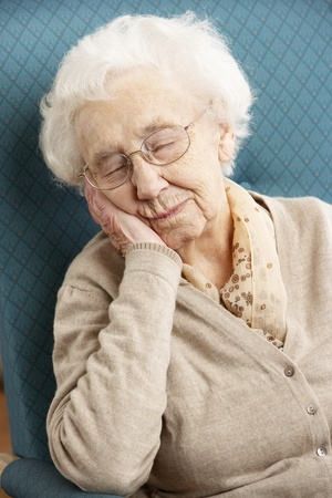 asleep chair: Senior Woman Resting In Chair At Home Stock Photo