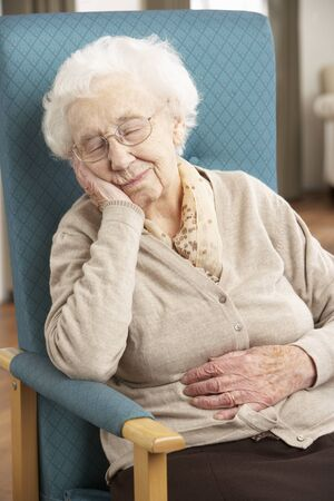 residental care: Senior Woman Resting In Chair At Home Stock Photo