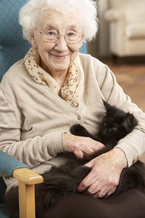 Senior Woman Relaxing In Chair At Home With Pet Cat Stock Photo - 9911187