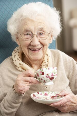 nineties: Senior vrouw te genieten van Cup of Tea At Home Stockfoto