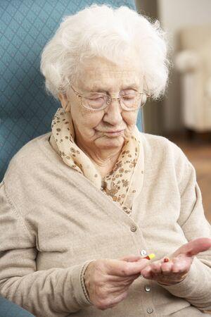 persona confundida: Mujer Senior confundida mirando medicamentos Foto de archivo