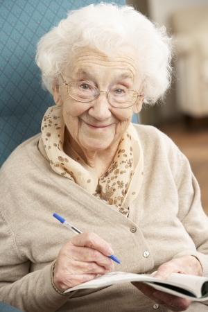 tercera edad: Mujer Senior relajante en silla en casa completar crucigramas Foto de archivo