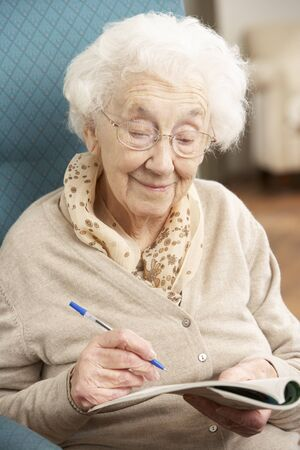 Senior Woman Relaxing In Chair At Home Completing Crossword Stock Photo - 9911210