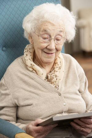 nineties: Senior Woman Looking At Photograph In Frame Stockfoto
