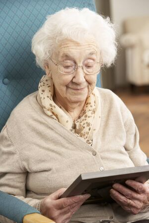 Sad Senior Woman Looking At Photograph In Frame photo