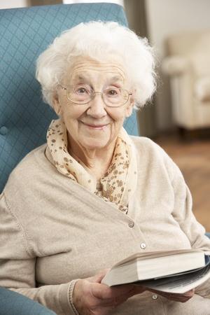 Senior vrouw ontspannen in stoel thuis leesboek