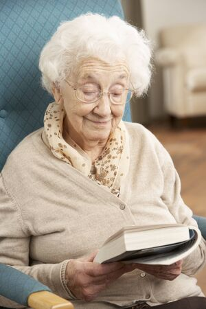 Senior Woman Relaxing In Chair At Home Reading Book photo