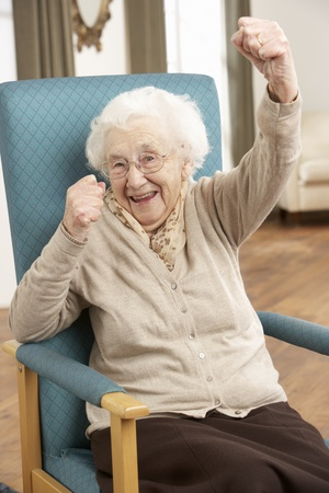 residental care: Senior Woman Celebrating In Chair At Home