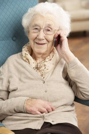 home phone: Senior Woman Talking On Mobile Phone Sitting In Chair At Home
