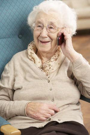 tercera edad: Senior mujer hablando por tel�fono m�vil sentado en silla en casa