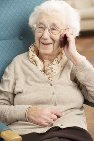 Senior Woman Talking On Mobile Phone Sitting In Chair At Home photo