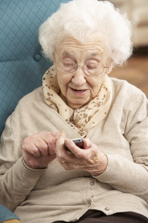 happy old people: Senior Woman Dialling Number On Mobile Phone Sitting In Chair At Home