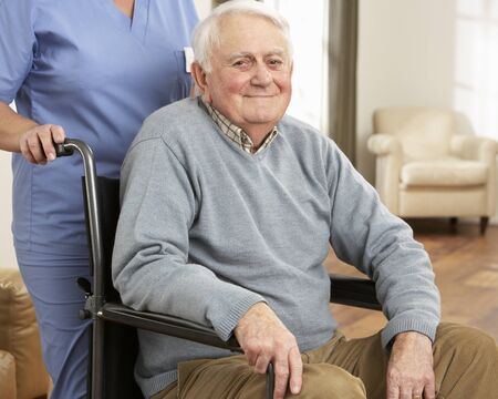 Disabled Senior Man Sitting In Wheelchair With Carer Behind photo