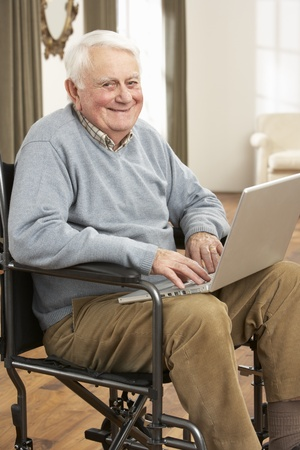 healthy seniors: Disabled Senior Man Sitting In Wheelchair Using Laptop Stock Photo