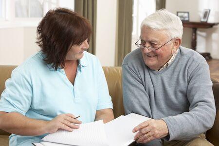 visitador medico: Hombre Senior en discusión con el visitante de la salud en el hogar