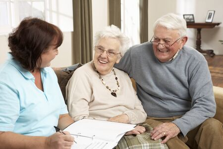 healthcare visitor: Senior Couple In Discussion With Health Visitor At Home Stock Photo