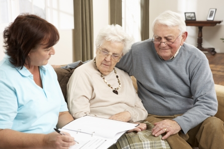 home healthcare: Senior Couple In Discussion With Health Visitor At Home Stock Photo