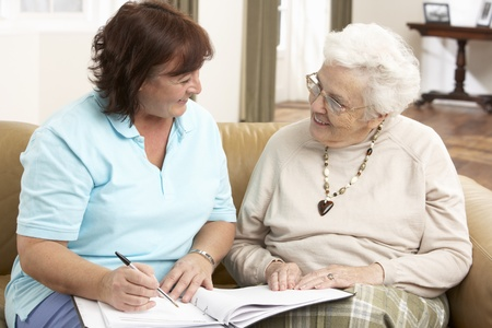 dos personas conversando: Mujer Senior en discusi�n con el visitante de la salud en el hogar Foto de archivo