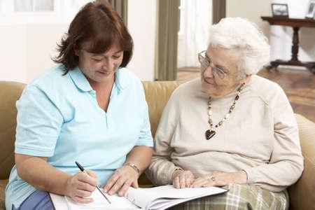 visitador medico: Mujer Senior en discusión con el visitante de la salud en el hogar Foto de archivo