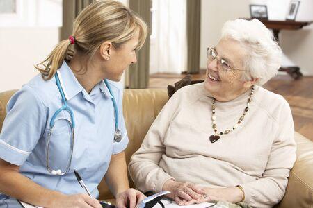 tercera edad: Mujer Senior en discusi�n con el visitante de la salud en el hogar Foto de archivo