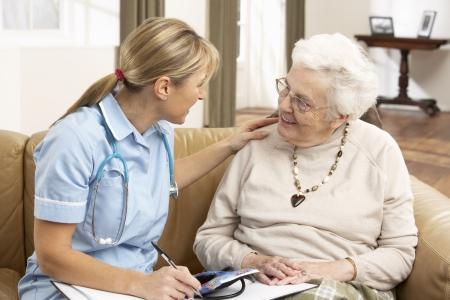 visitador medico: Mujer Senior en discusi�n con el visitante de la salud en el hogar Foto de archivo