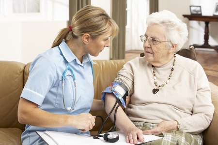 healthcare visitor: Senior Woman Ihaving Blood Pressure Taken By Health Visitor At Home Stock Photo