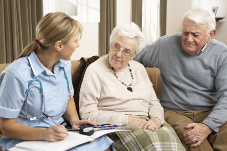Senior Couple In Discussion With Health Visitor At Home photo