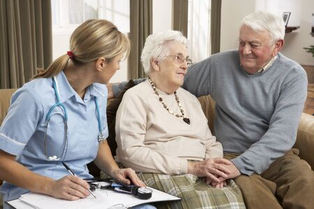 Senior Couple In Discussion With Health Visitor At Home Stock Photo - 9911212
