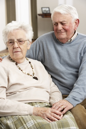 Senior Man Consoling Wife At Home photo