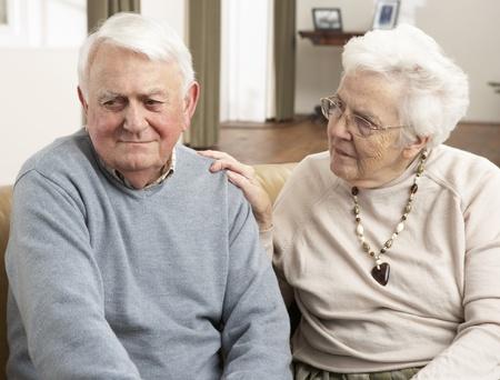hombre preocupado: Mujer mayor que consuela marido en casa